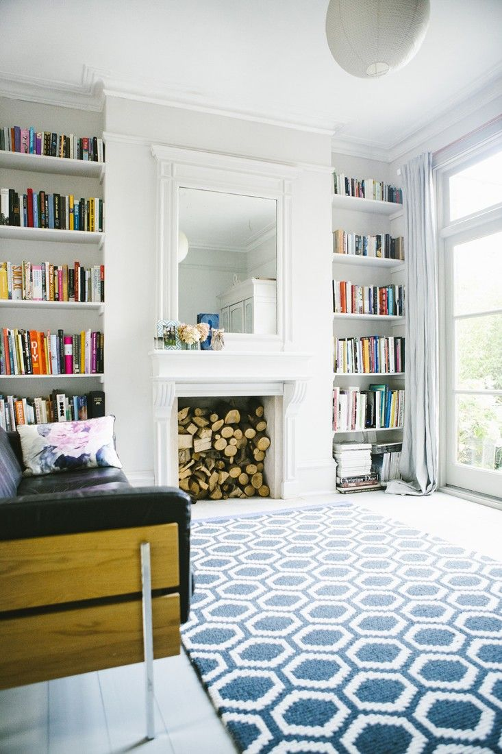 Bookshelves in alcoves on either side of fireplace in living room of Victorian house renovation by Imperfect Interiors