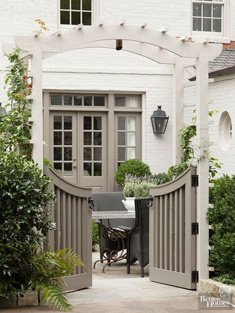 Curved Double Garden Gate with Arbor and Hedge - Painted White Brick House
