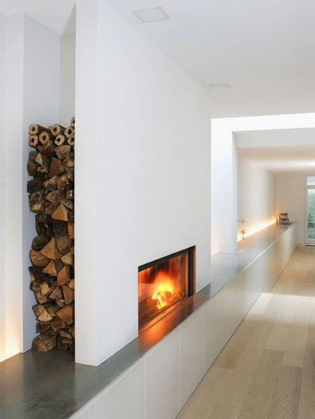 """Moderne """"open""""haard - open en gesloten te branden met een schuifdeur die omhoog kan. Houtopslag achter de verlengde wand."""