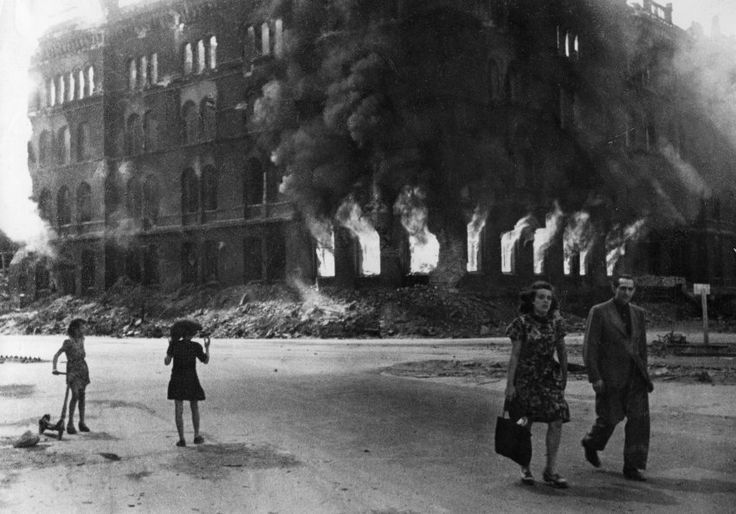 In the streets of Berlin during the last days of the Nazi regime, a couple walks past a burning police station.