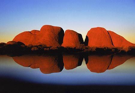Kata Tjuta rock formations reflected in lake at dusk, Uluru-Kata Tjuta National Park, Australia (© Kul Bhatia/Corbis The large formations dwarf everything around them in this national park. Also a spiritual site for the Aboriginal population. The lighting changes from dawn to dusk making it an awesome display of beauty hour to hour...