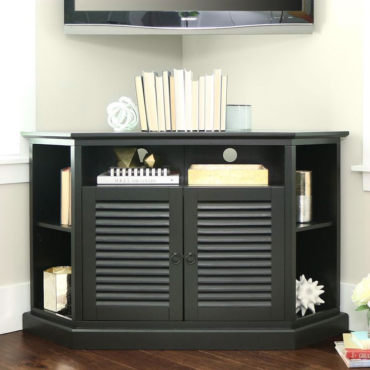 This black wood cornered TV stand is a great space-saving solution. The console features multiple shelves, able to hold DVD players and game systems. The stand can accommodate most TVs up to 55'. A perfect solution for living rooms and many bedrooms.