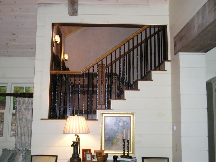 Heart Pine Original Patina Stairway combined with milled surface heart pine panel inlays, trim, reveals, step treads, handrails with iron balusters. Millwork by Vintage Lumber Sales in Gay, GA