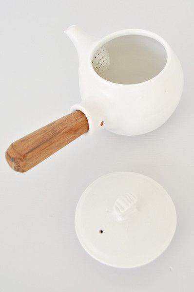 White, Japanese ceramic teapot with pouring spout and teak handle. The handle has been hand carved and shaped for easy pouring. Teak is a relatively water-resis