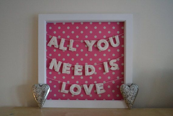 Framed All You Need Is Love mini bunting, made from Olive and Daisy linen (with rose pink and grey hearts). Threaded onto handmade pink and white bakers twine and displayed against a pink and white polka dot card background within a deep box frame.  Each letter is a mini quilt! There is a layer of wadding sandwiched between two layers of the linen fabric. The letters are machine-sewn and then I cut each one out by hand.  The frame is 12 x 12/30 x 30cm.