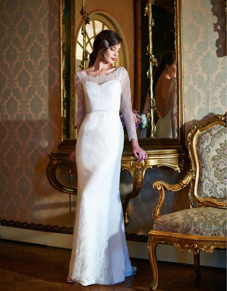 Our Claudia gown is long-sleeved and fitted in crepe satin and Spanish lace, with ribbon embroidery, laser cut petals and pearl-work on the hem, hand-beaded pearl encrusted belt in the waist and plunging back edged with lace scallops.