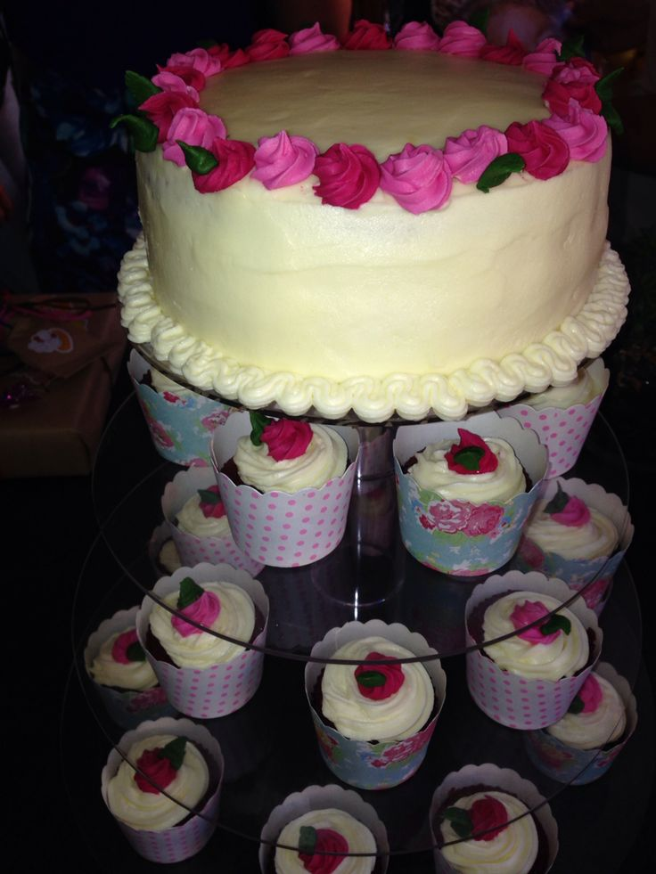 Red velvet and cream cheese frosting cake and cupcakes. Sugar rose decorations.