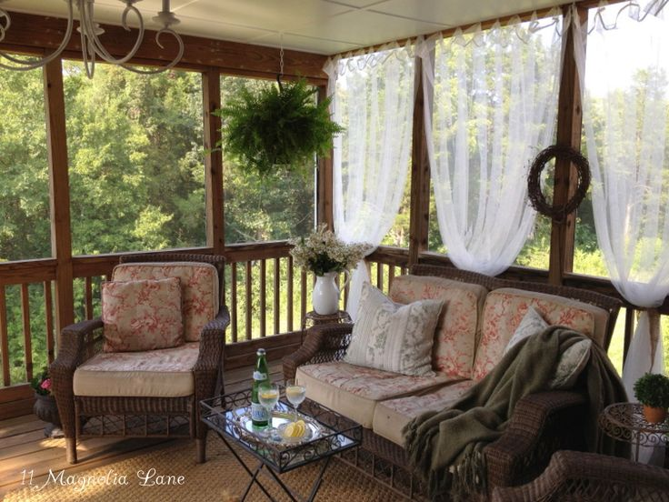 Screened porch is decorated with inexpensive sheer panels from Ikea for a light and airy look.