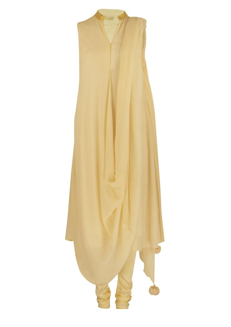 An elegant, draped off white kurta set with gold detailing around the neckline by Nikasha at EVOLV!