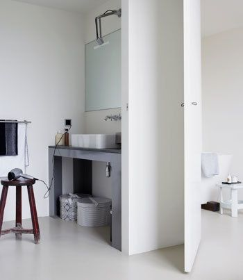 Relaxen - vtwonenPlafondhoge klapdeuren scheiden de slaap- en relaxruimte van de natte ruimte. Als de deuren dicht zijn, is het voor het oog gewoon een witte wand. Dat geeft rust. Als de deuren openstaan is dit een grote multifunctionele relaxruimte met een hoge gezelligheidsfactor: als de een in bad ligt en de ander op bed, kun je toch met elkaar praten of een film kijken.