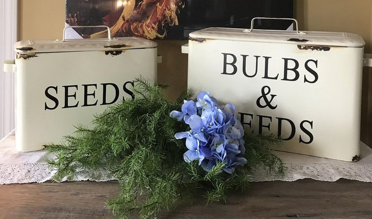 """These vintage-inspired metal boxes with lids are as practical as they are pretty. Use these Vintage Enamel Bulbs & Seeds Bins with Handles, Set of 2 to store just about anything you like, anywhere you like. Fill them with goodies and set them on the counter or on a shelf for a burst of farmhouse-fresh style. The distressed enamel finish adds an aged look that completes the overall vintage appeal of set.    They measure 18-3/4""""L x 7-1/2""""W x 12-1/4""""H & 15-3/4""""L, 6-1/2""""W x 11""""H."""