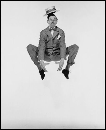 """LEAPING LEGS of Hollywood: This dancer displays a pretty good high jump while holding an invisible watermelon and balancing a hat on his head. He's comic actor -- Ray Bolger. Photo taken from """"Philippe Halsman's Jump Book"""" (1959) — reissued by Abrams in 1986."""