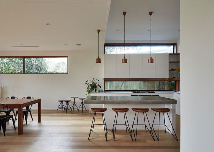 Copper lights concrete bench kitchen at Step Down House — Bijl Architecture