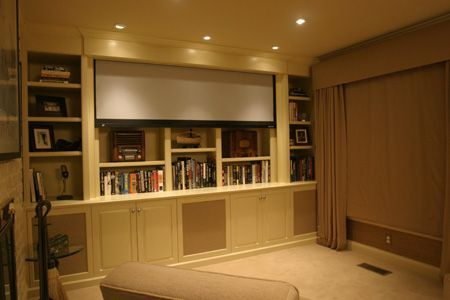 Hidden projector screen allows this space to be utilized as both a home theatre and library.