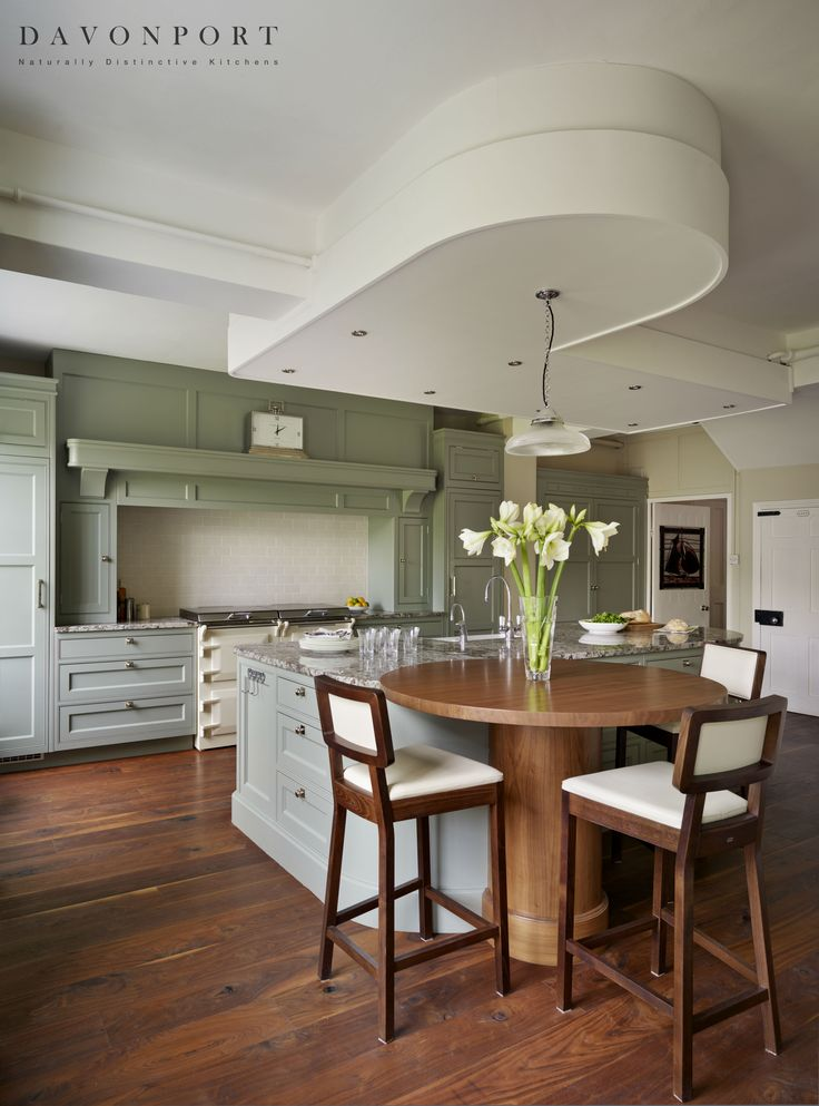 The warmth of the walnut table matches the walnut floorboards used throughout the kitchen. These rich accents of colour look stunning set against the softness of the green used on the kitchen cupboards.
