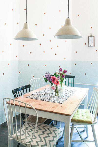 Süße Küche mit verspielter Wandgestaltung: Die weiß-hellblaue Wand zieren gold-kupferne Tupfen! ♥ Schön finden wir auch die gemusterten Sitzkissen und die bunten Blümchen auf dem Tisch.