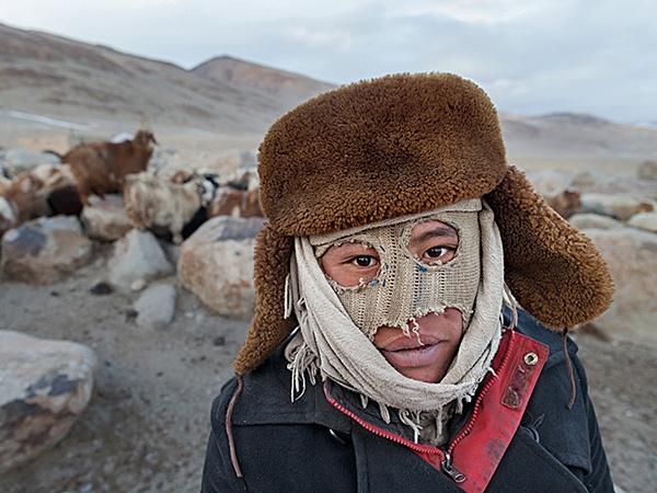 Rosman Baig si protegge dal freddo con un passamontagna improvvisato in un accampamento invernale vicino al confine con la Cina. Pecore   e capre sono un'importante risorsa per i nomadi kirghizi, ma accudirle d'inverno è un lavoro duro.  Fotografia di Matthieu Paley
