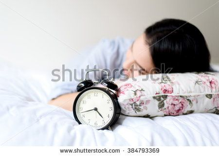 Selective focus on antique black alarm clock in front of young and beautiful asian girl on the bed. - stock photo