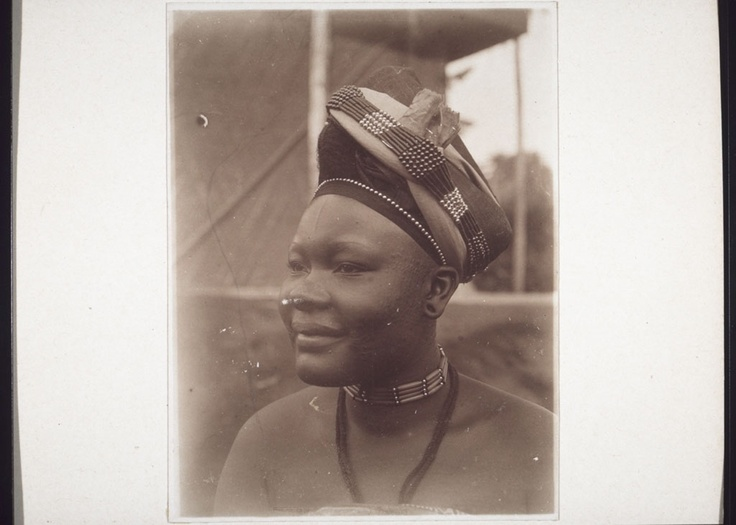"""""""Hanna Ntue, a daughter of the King.""""  Details    ID# impa-m28725  Source E-30.30.043   Part of Historical Photographs from the Basel Mission   """"Cameroon. Grasslands. Bamum. 1. Brothers and sons of the King. 2. Sisters and daughters of the King. 3. Ngutane, Njoya's oldest daughter, 4. Wives of the King.""""   mission 21 / Basel Mission   Creator Wuhrmann, Anna (Ms)"""