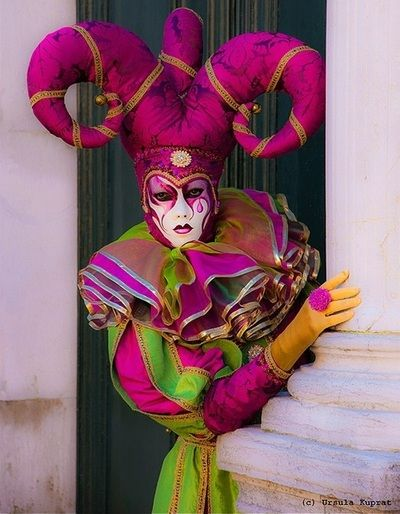 A woman in a jester's costume peeks out from behind a column.