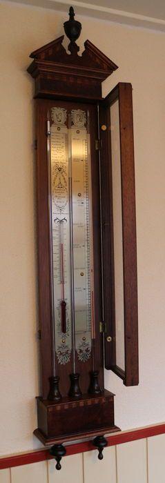 En bon état, presque pas de traces d'utilisation Ce type de baromètre contient un Huygens et un baromètre de Torricelli et avec un thermomètre, ils sont placés dans un boîtier en bois joliment décoré.  La porte en verre a également un profil vertical La boîte de mot se réfère à la boîte (occultable) sur le fond dans lequel i.a. est placé le réservoir de mercure pour le baromètre de Torricelli. Ce baromètre a été effectué dans les années 1950 dans le studio du célèbre baromètre du cabinet...