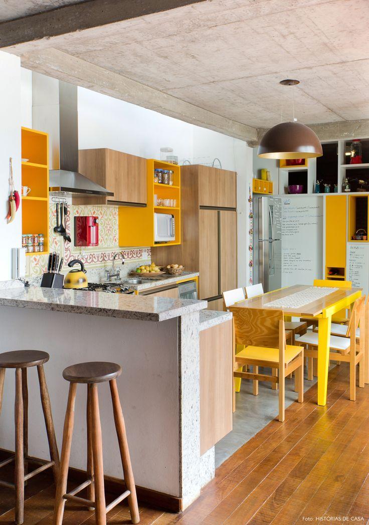 cozinha integrada com armários amarelos, piso de cimento e teto de concreto, além da faixa de ladrilhos hidráulicos na parede