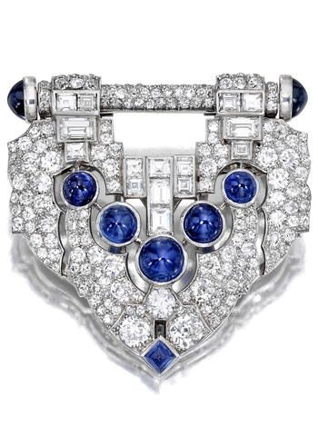 An Art Deco sapphire and diamond clip, J.E. Caldwell circa 1930. The geometric plaque of pierced design, set with old and baguette-cut diamonds, enhanced by cabochon sapphires; signed JEC & Co., no. J1808; estimated total diamond weight: 9.00 carats; mounted in platinum.