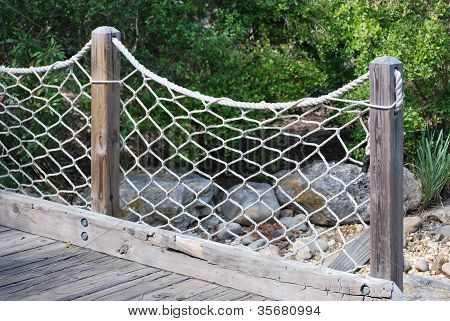 Nautical rope made into a fence.  This may work in front of the retaining wall in the upper seating area above the seawall.