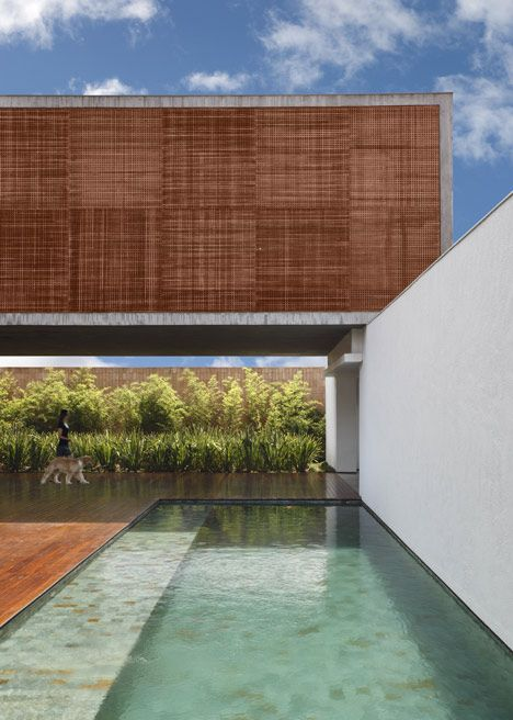 BT House by Studio Guilherme Torres in Maringa, SP, Brazil -- Unlike the opaque brick walls of the lower level, this top floor is clad with latticed mashrabiya screens (carved wood latticework) that bring light and ventilation into the family's bedrooms, but also maintain privacy.