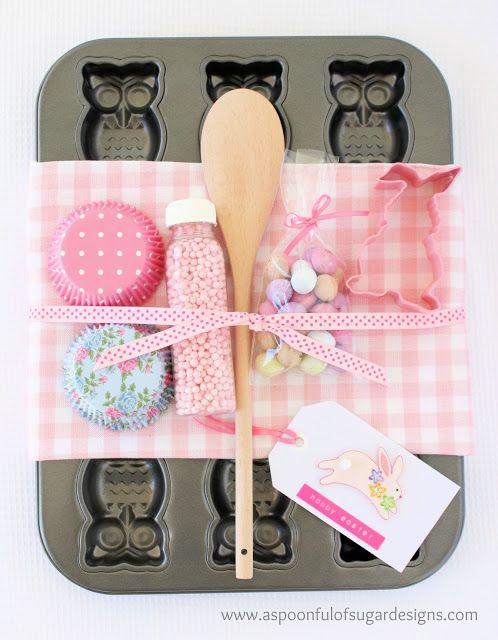 Cosa comprare:  tortiera, cucchiaio di legno, fodere del bigné, canovaccio, adesivi di Pasqua, mini uova di Pasqua.  Inoltre:  tag trasporto bianco, etichetta Dymo, cookie cutter, spruzza cottura o perle, nastro, sacchetto di cellophane.  Come:  Mettere le uova di Pasqua in un sacchetto di cellophane e cravatta con il nastro. Avvolgere l'asciugamano tè intorno alla tortiera. Posizionare il cucchiaio, fodere, uova, e le forniture di cottura sulla parte superiore, e legare con un nastro…