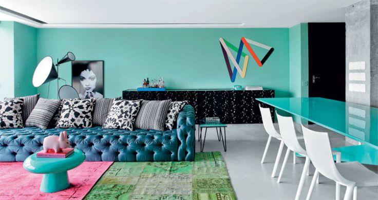 Na sala decorada por Guilherme Torres, o verde-água da parede se combina ao sofá azul-petróleo, tons da moda.