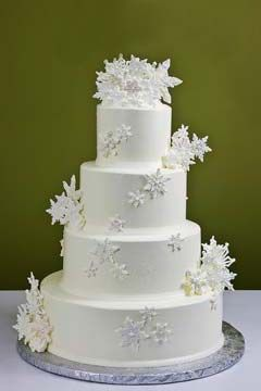 Simple four tier, winter white Christmas snowflake wedding cake is decorated with large snow white handcrafted and edible cascading snowflakes and crowned with a gorgeous snowflake wedding topper. From www.jacquespastries.com #wedding #cake