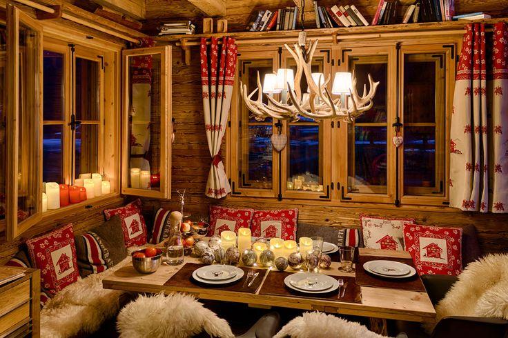 MIse en place natalizia della tavola con candele led rosse e avorio, tende e cuscini che ricreano l'atmosfera da chalet