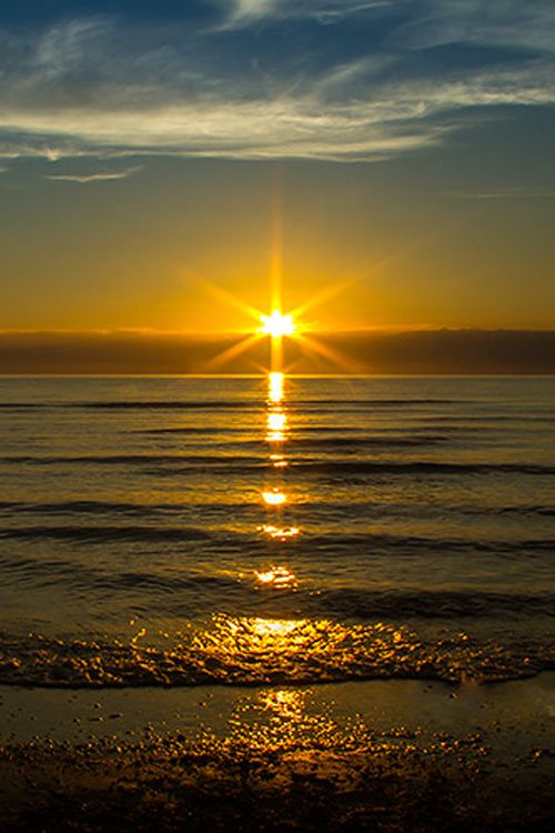 Light; In this image the water is used to reflect the rising sunlight. There is a glare surrounding the sun.
