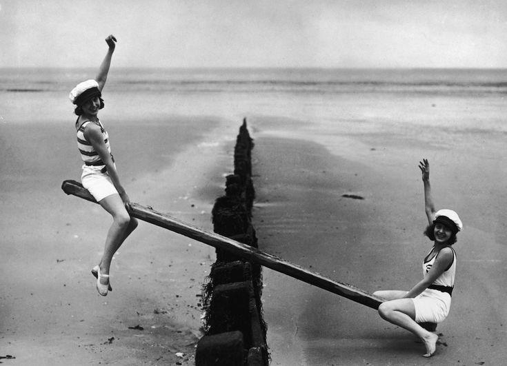 IlPost - Altalena in spiaggia - Due ragazze su un'altalena improvvisata in una spiaggia inglese, nell'aprile del 1930.  (Topical Press Agency/Getty Images)