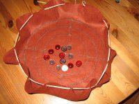 Spiele im Beutel - wie im Mittelalter. Der Beutel enthält die Spielsteine und ist ausgebreitet gleichzeitig ein rundes Spielbrett.