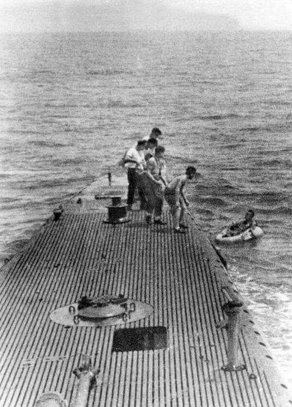 Crew of USS Finback pulling downed airman Lieutenant (jg) George Bush from the water off Chichi Jima, Bonin Islands, 2 September 1944.
