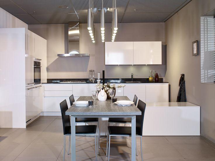 Ziet deze witte keuken er niet ontzettend strak uit? Gaaf in combinatie met het zwarte aanrechtblad en de zwarte stoelen die net zo dun zijn als het werkblad.