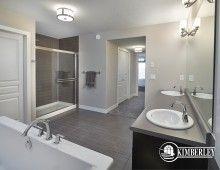 Master Ensuite (master bathroom). Dark-stained custom cabinets, large tiled shower, freestanding soaker tub. Onyx floorplan as built in Keswick on the River, by Kimberley Homes, Edmonton.  #interiordesign #newhomedesign #homedesign #newhome #customhome #yegre #buildwithkimberley #kimberleyhomes #bathroom #bathroomdesign #bathroomideas #freestandingtub #vanities
