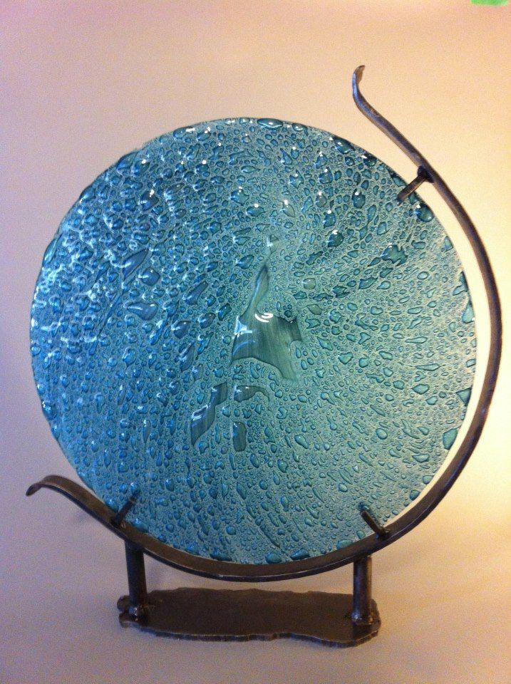 """Maelstrom"", Kiln-worked window glass combined with metal oxides. 16"", wrought iron stand. Big Field works with a local window manufacturer to use glass offcuts destined for landfill as the raw material for the majority of her art and functional works."