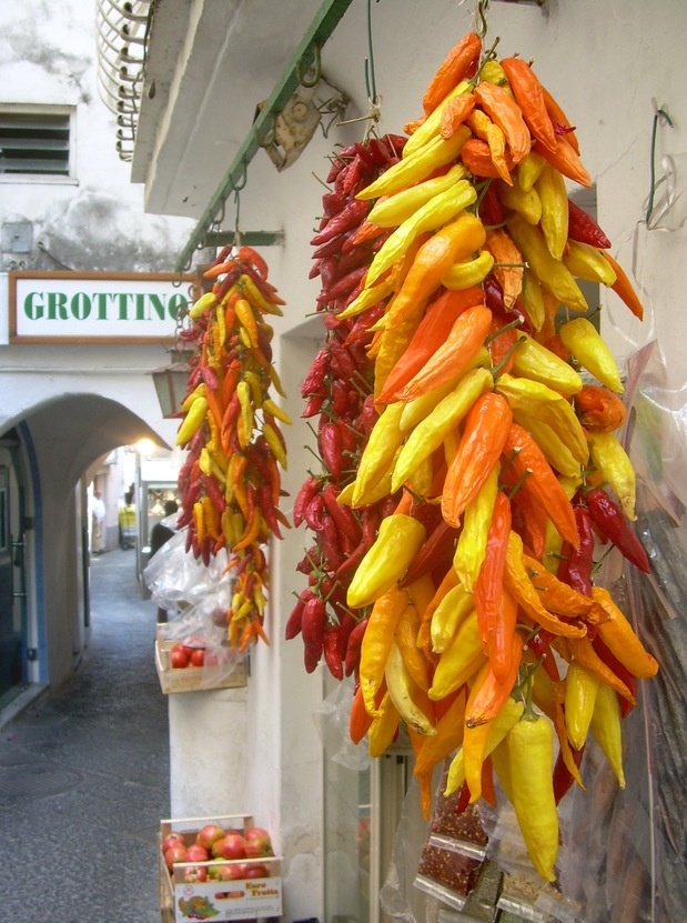 Bunches of chili peppers hanging in the street, Italy.