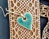Gorgeous handmade heart pendant from ButtonMad. Soft blue glaze. The reverse is unglazed white clay with a lace pattern in relief. Available on Etsy.