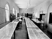 """Scholars assembling and examining the Dead Sea Scrolls fragments in what became known as the """"Scrollery"""" room of the Palestine Archaeological Museum."""