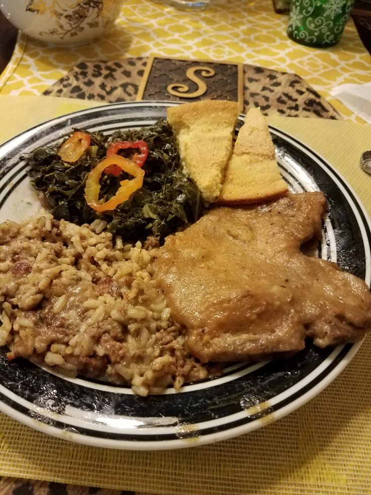 Smothered porkchop and gravy dirty rice and collard greens.