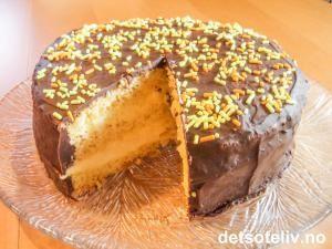 """Oppskriften på """"Go'kake"""" er hentet fra spalten """"Lesernes beste kaker"""" i et gammelt Allers-ukeblad. Om oppskriften skriver innsenderen: """"Sender oppskrift på min yndlingskake som jeg ganske enkelt kaller Go'kake"""". """"Go'kake"""" består av luftig sukkerbrødsbunn som fylles med en kjempenydelig sitronkrem. Kaken dekkes med sjokoladeglasur og kan pyntes med kakestrøssel med appelsinsmak (se bildet), hakkede mandler eller mokkabønner."""