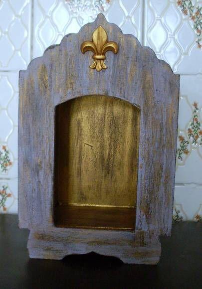 Oratório de MDF, com pintura lilás e dourada, acabamento em pátina. Aplique dourado em forma de flor-de-lis na parte frontal.
