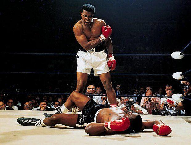 """Neil Leifer   """"Wstawaj i walcz, frajerze"""", 1965   Pojedynek rewanżowy pomiędzy Muhammadem Alim a Sonnym Listonem - Ali broni w tej walce tytułu mistrza wagi ciężkiej."""