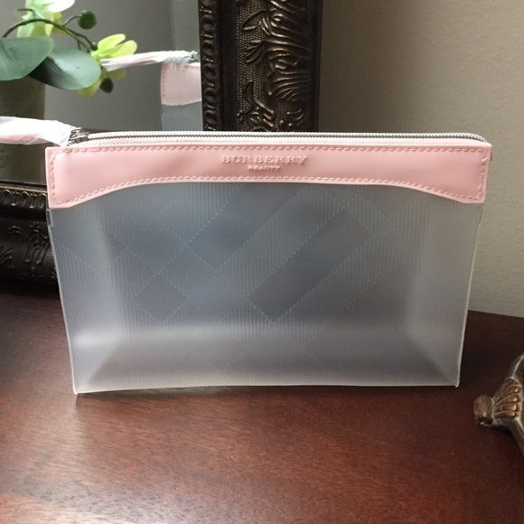 "Burberry Clear Cosmetic Bag Cute and practical makeup bag by Burberry. Clear bag with and all over novacheck print. Pink trim on the top. ""Burberry Beauty"" on the top and zipper pull. Perfect for traveling and flying since it's see-through. Also available in grey/silver. Brand new, never used, still in original packing. Burberry Bags Cosmetic Bags & Cases"