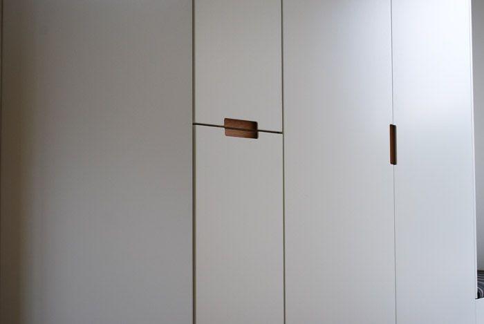 Platsbyggd / måttbeställd garderob i vitlackerat utförande med integrerade grepp i oljad ek.Optimal förvaring från golv till tak som utnyttjar hallutrymmet maximalt.