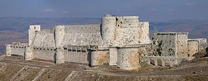 A stone castle with two high curtain walls, one within the other. They are crenelated and studded with projecting towers, both rectangular a...